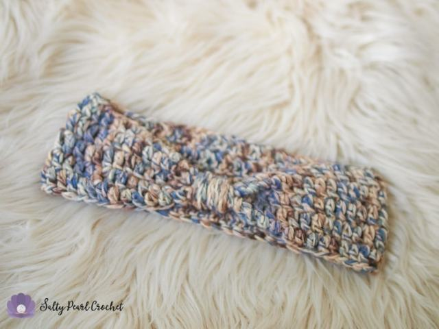 An easy crochet ear warmer laid on a sheepskin rug.