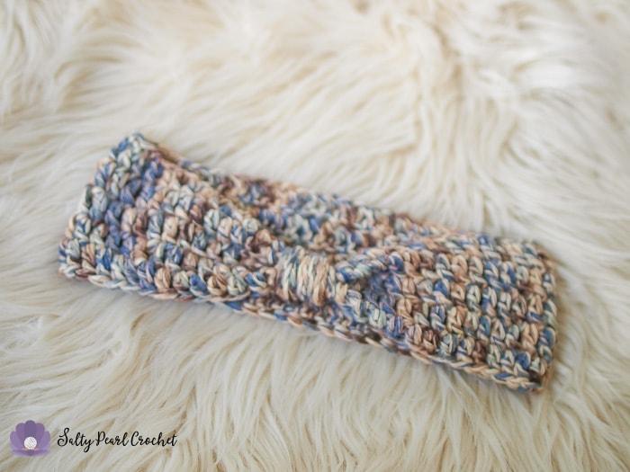 An easy crochet ear warmer laid on a sheepskin rug.