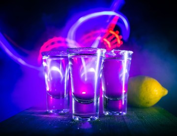 three shots of clear liquor on a table with a lemon