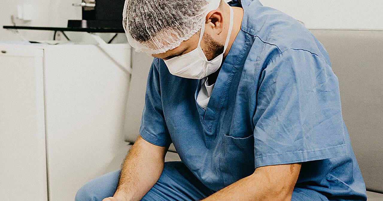 Profesional sanitario con mascarilla cabizbajo visiblemente agotado