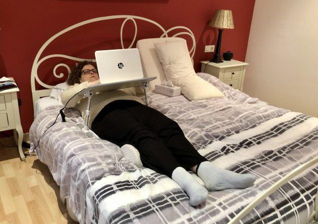 Mujer trabajando con un ordenador portátil tumbada en la cama. Es paciente con dolor crónico