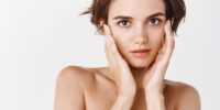 Women beauty. Tender girl standing half naked and touching healthy no makeup skin, showing hydrated and smooth face after facial cleansing gel, white background.