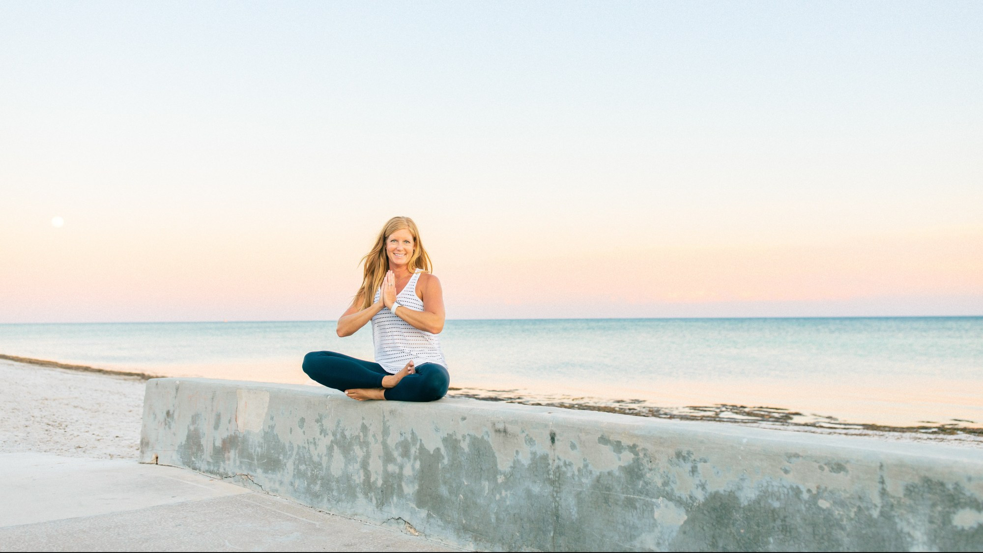 woman sitting on wall in a yoga position with a sunset behind her