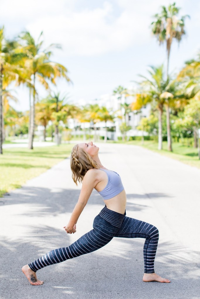woman doing a yoga pose in Key West surrounded by palm trees