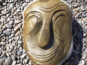 Smiling face of a man in stone sculpture made by Edwin Oraw.