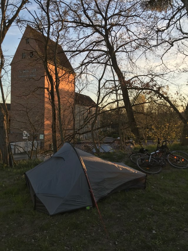 A picture of a tent set with a church in the background on sunset.