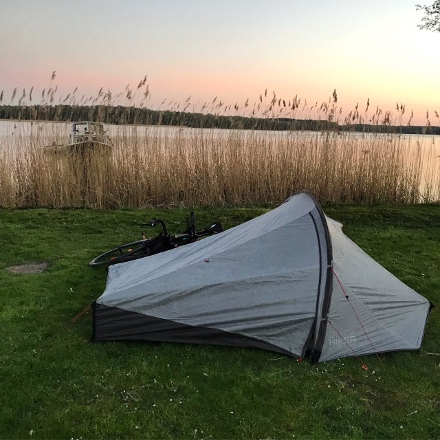 A picture of a tent set on a camp site by the lake
