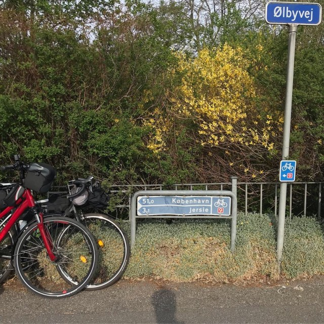 A picture of two bikes standing close to a sign that shows the distance remaining to Copenhagen.