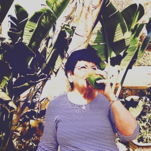 mom enjoying green smoothie outside