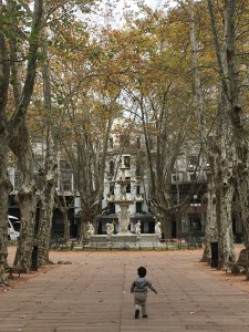My toddler races down a leafy Plaza Matriz, Montevideo, Uruguay