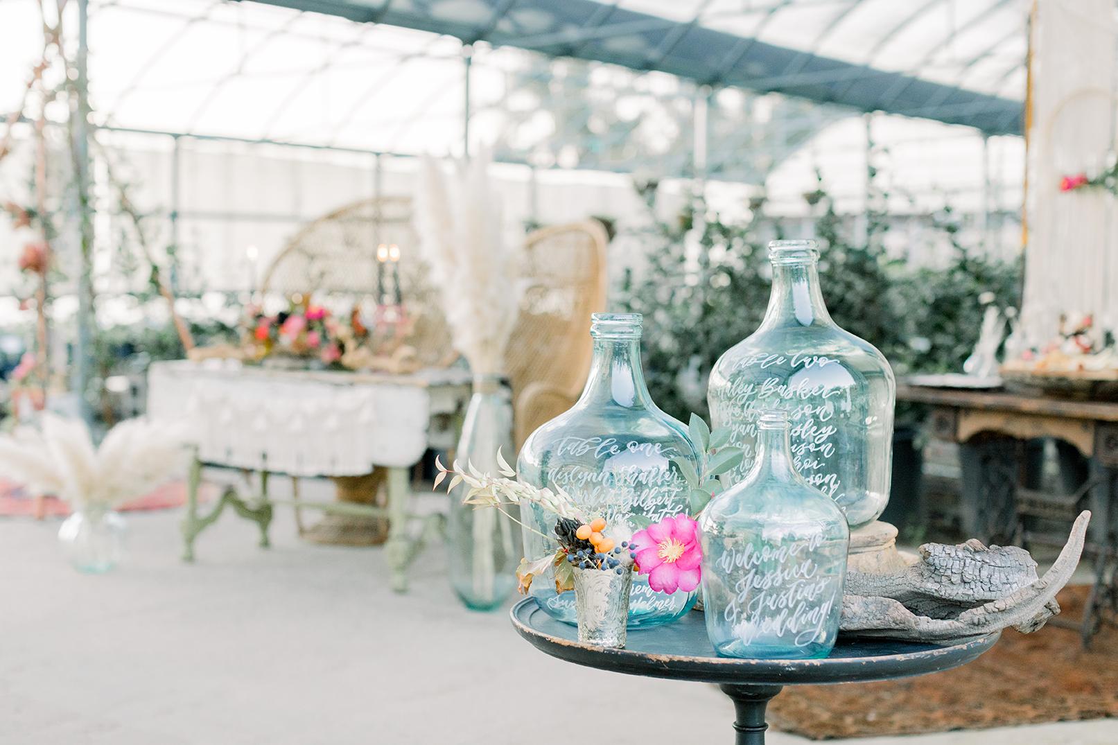 SWP-TheGreenhouse Boho Wedding Inspiration-388SWP Sam Allen Creates Seating Chart on Blue Glass Bottles