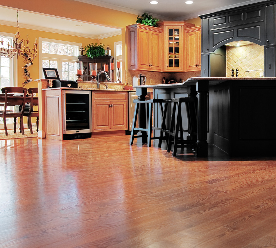 Home interior shows a large expanse of wood flooring in the foreground and a kitchen and dining room in the background. Horizontal format.