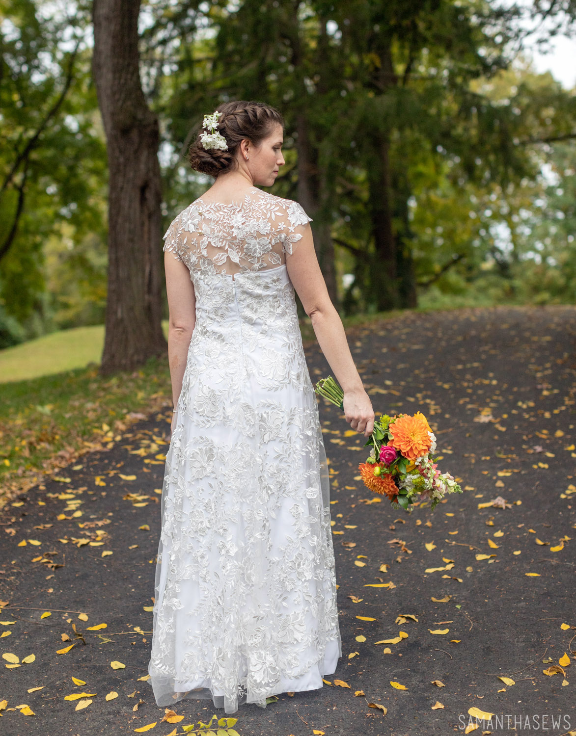 back of handmade wedding dress sewn with lace fabric, showing pearl buttons