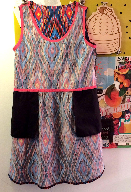 black ikat-print dress with pockets and pink bias tape
