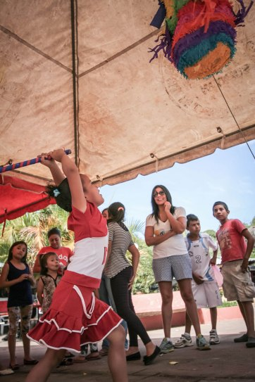 Young girl reaching to hit the piñata