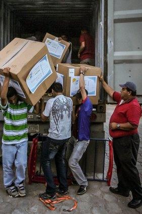 Local men help unload the donations