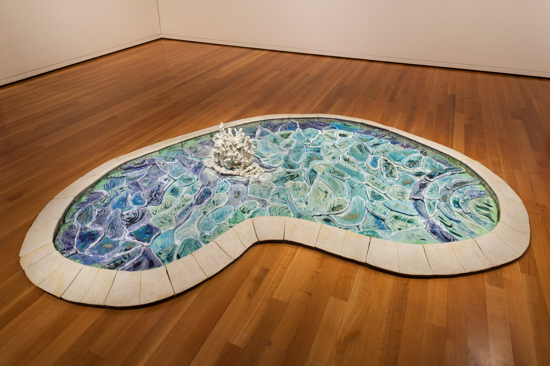 A photograph of a kidney bean-shaped pool sculpture on a wood floor, each ripple and refraction of light is represented as an immutable piece—fitted together like a puzzle—with blue and green glazes and is punctuated with a foamy burst in the middle, invoking the presence of a swimmer.