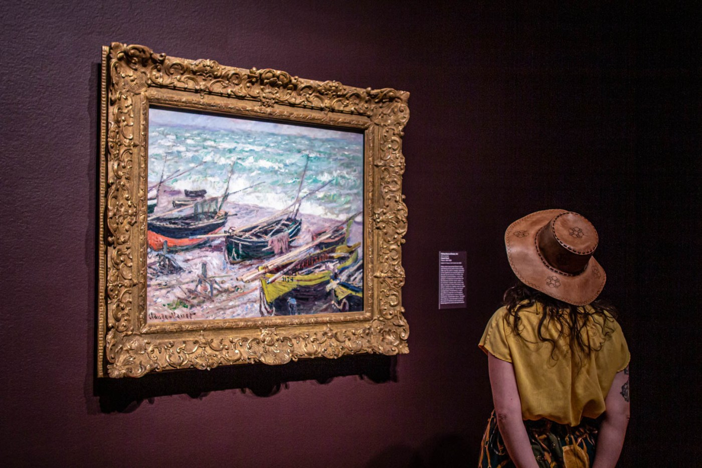 Image of a person looking at a Monet painting of fishing boats on a shore