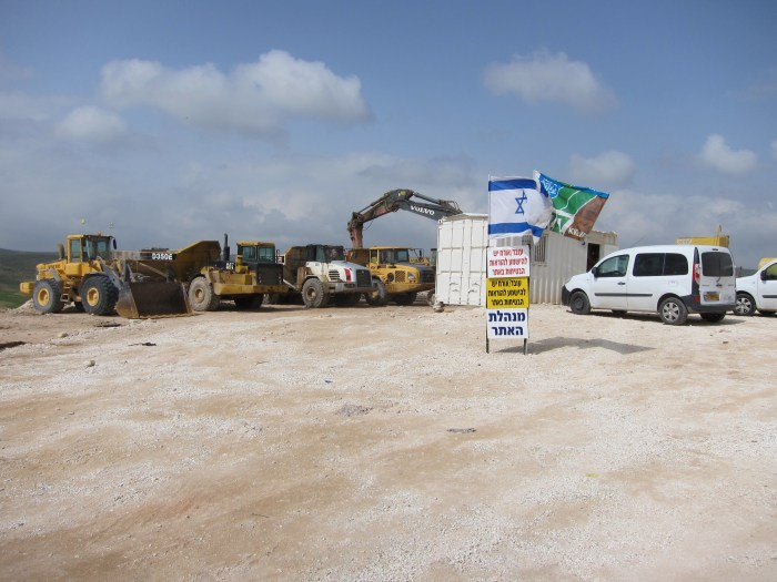 Bulldozers set to demolish Palestinian Bedouin village of Um El Heran, Al-Naqab desert. The village is to be destroyed in preparation for the construction of a Zionist settlement. The Jewish National Fund (JNF) flag flies alongside the Israeli flag.