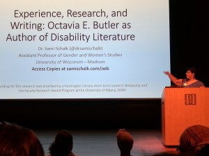 """Wide shot of Dr. Schalk on a darkened stage at the Octavia E. Butler Studies Conference at the Huntington Library. She is standing behind a podium in the lower right corner of the image, gesturing with her hand to the screen behind her. The large screen contains her talk title """"Experience, Research, and Writing: Octavia E. Butler as Author of Disability Literature"""" in large font above her name, title and contact information in smaller font. At the bottom of the image a few heads of audience members are visible."""