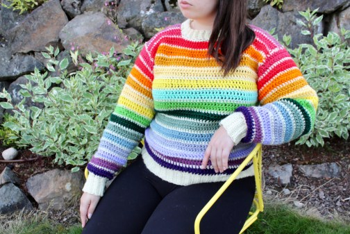 Evelyn is sitting down wearing a rainbow crochet sweater