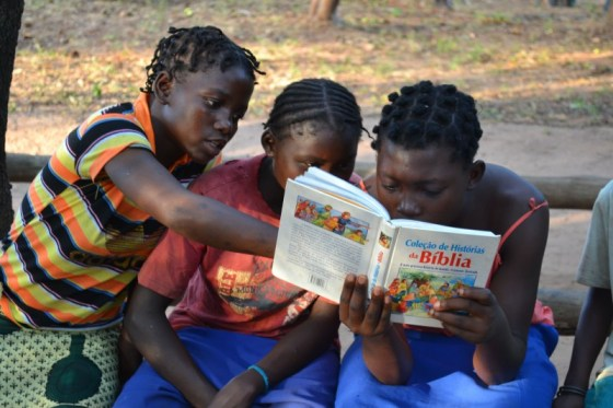 Rimbudzai, Mariamo and Angelina  excitedly reading the story of Esther in the Portuguese Children's Bible