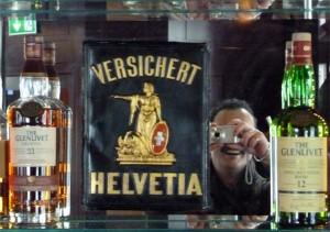 Stilleben mit Whisky, Blechschild und Sammler