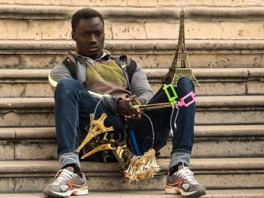 Czarnoskóry mężczyzna siedzi na schodach z figurkami wieży Eiffla na sprzedaż, jako symbol Jak relacja sprzedający-kupujący utrudnia sprzedaż
