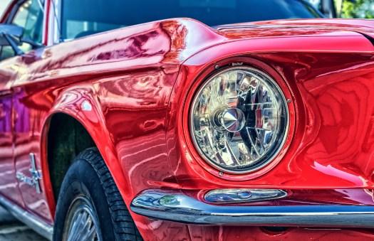 Przód czerwonego samochodu z reflektorem, jako symbol Ustalania Ceów