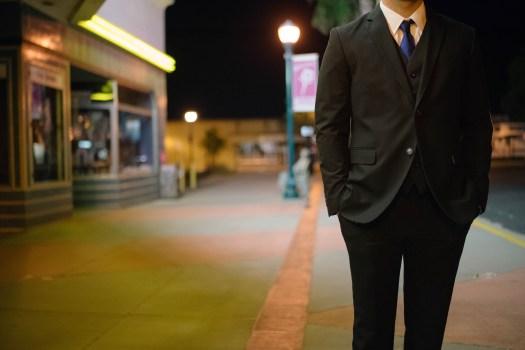 Mężczyzna wieczorem na tle sklepów, ulicy, ale na zdjęciu nie ma głowy, jako symbol niepewna samoocena