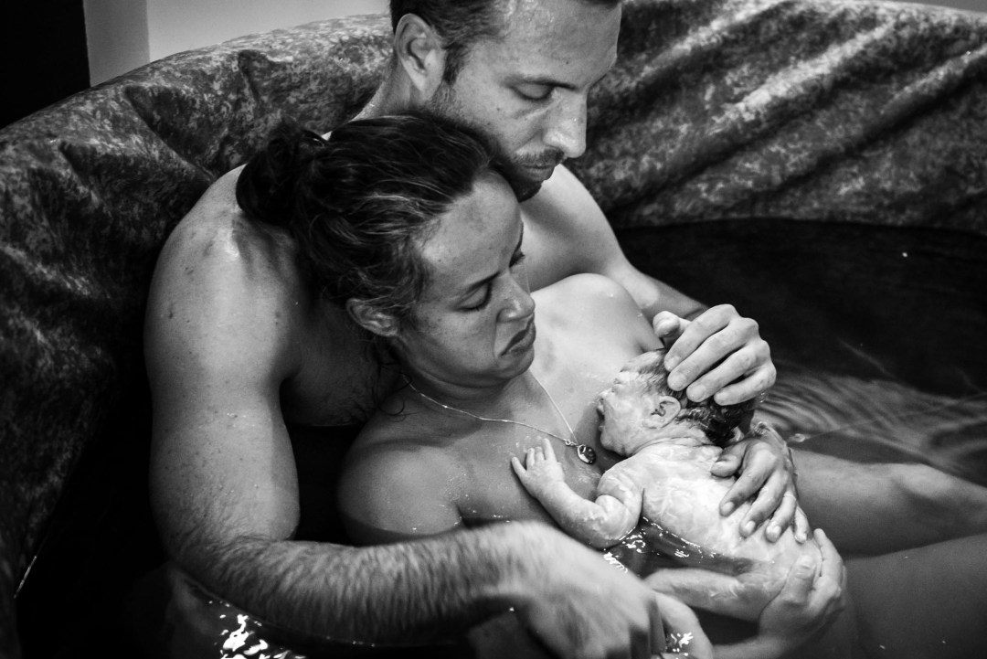 newborn on mom's chest after natural water delivery, with dad holding infant, skin to skin