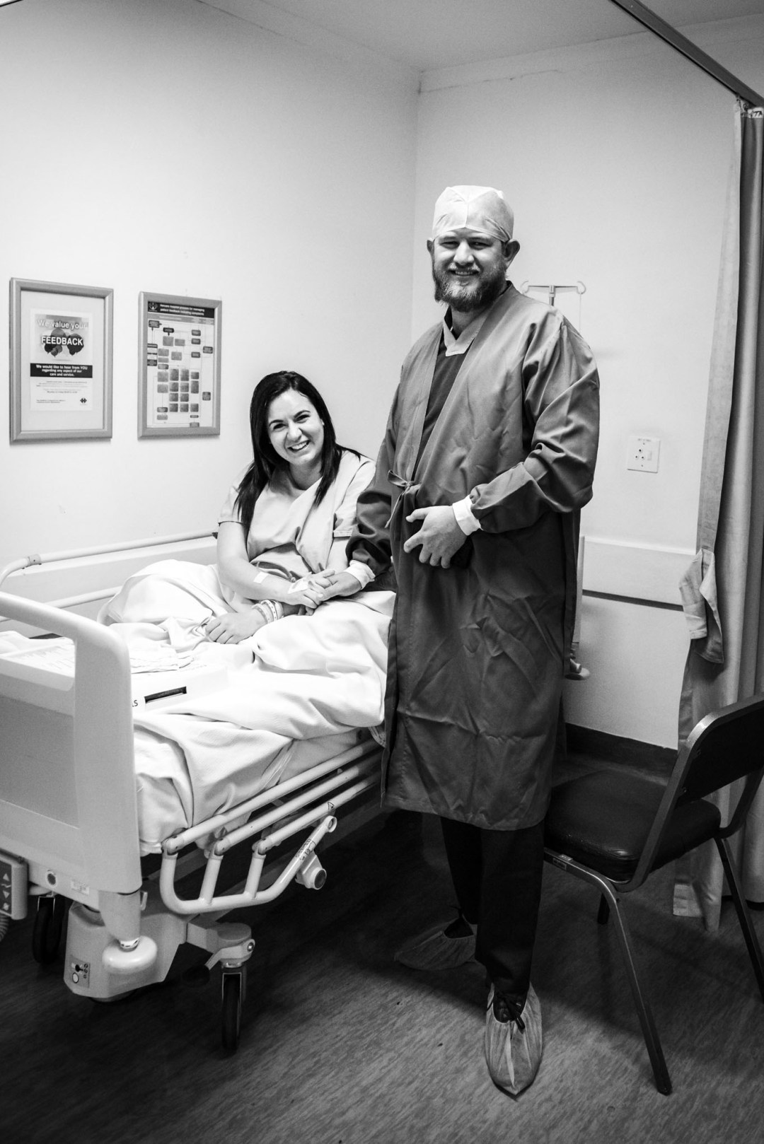mom and dad smiling and holding hands before caesarean birth