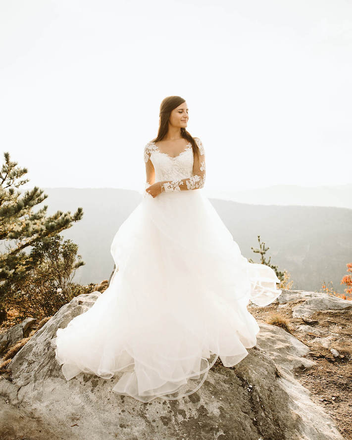 bride holding dress and spinning on table rock