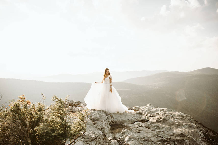 bride holding dress at table rock
