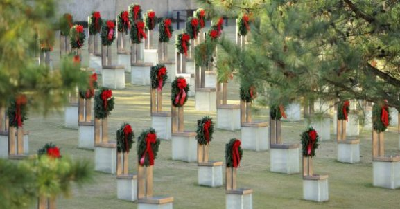 Wreaths adorn empty chairs, each memorializing a victim of the bombing.