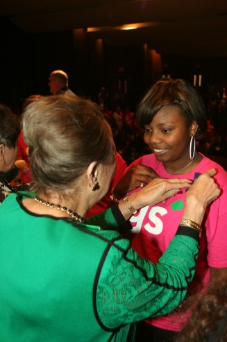 Girl Scout Alumna and arts advocate Aaronetta Pierce pins a Gamma Sigma Girl  during the Nov. 12 Investiture Ceremony.