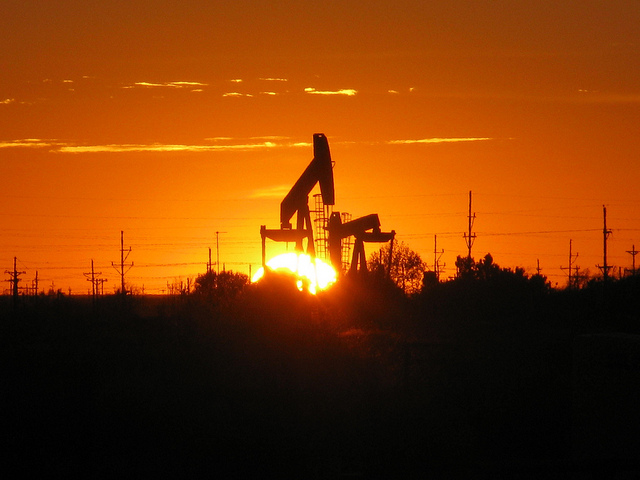 """The sun sets behind a pump jack near Midland, TX. The oil and gas industry has many parts, from exploration and extraction (""""upstream"""") to processing and transportation (""""downstream""""), which often happen in close proximity to one another. These active wells are mere yards from wells being developed. Ryan Hill, Epidemiologist, NIOSH Alaska Pacific Regional Office."""