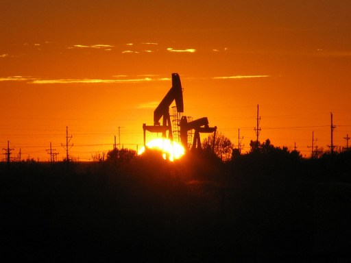 """The sun sets behind a pump jack near Midland, TX. The oil and gas industry has many parts, from exploration and extraction (""""upstream"""") to processing and transportation (""""downstream""""), which often happen in close proximity to one another. These active wells are mere yards from wells being developed. Ryan Hill, Epidemiologist, Alaska Pacific Regional Office"""
