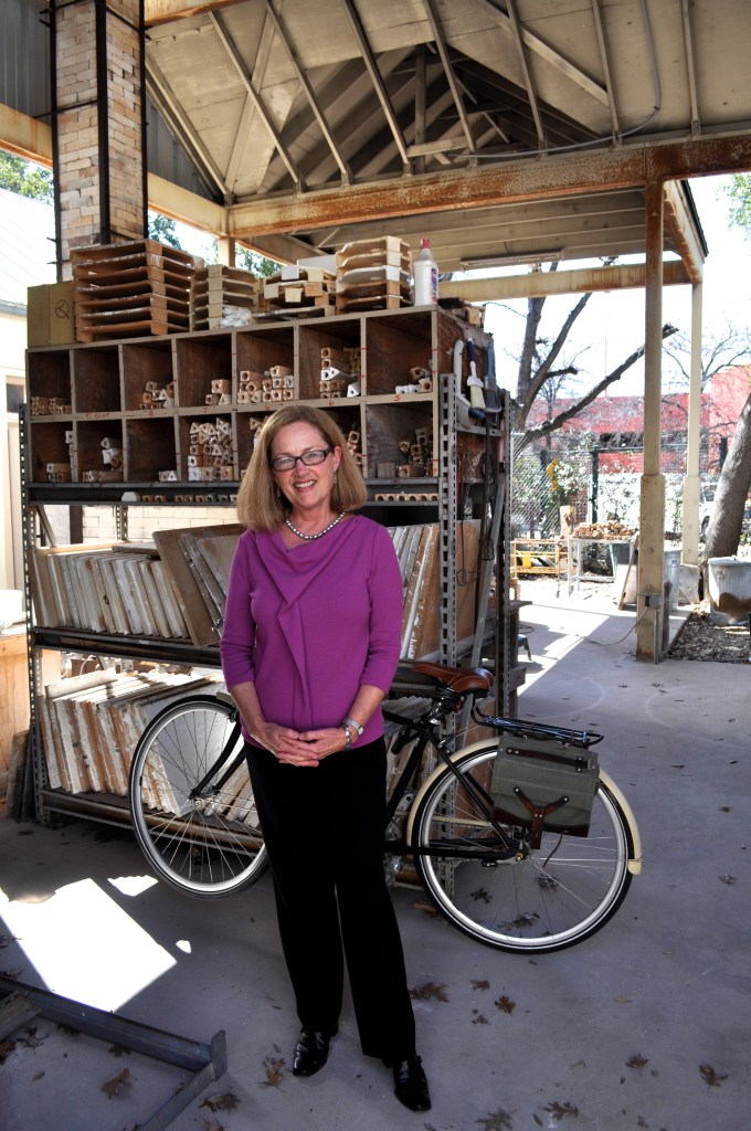 President and CEO of the Southwest School of Art Paula Owen stands amid supplies and kilns at the outdoor studio space at the school. Photo by Iris Dimmick.