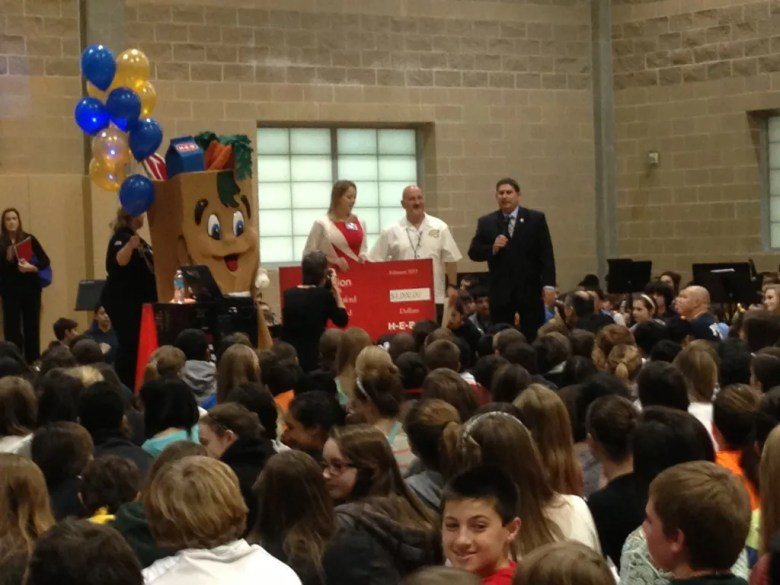 The HEB Buddy and Kimberly Harle present a check to  Dr. Barry Lanford while Superintendent Brian Gottardy expresses his appreciation. A see of middle school students await another chance to cheer.