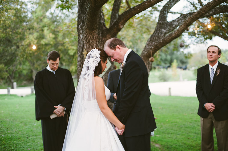 """Colleen & Will say """"I do"""" under a towering Pecan tree. Photo by Christine Sargologos."""
