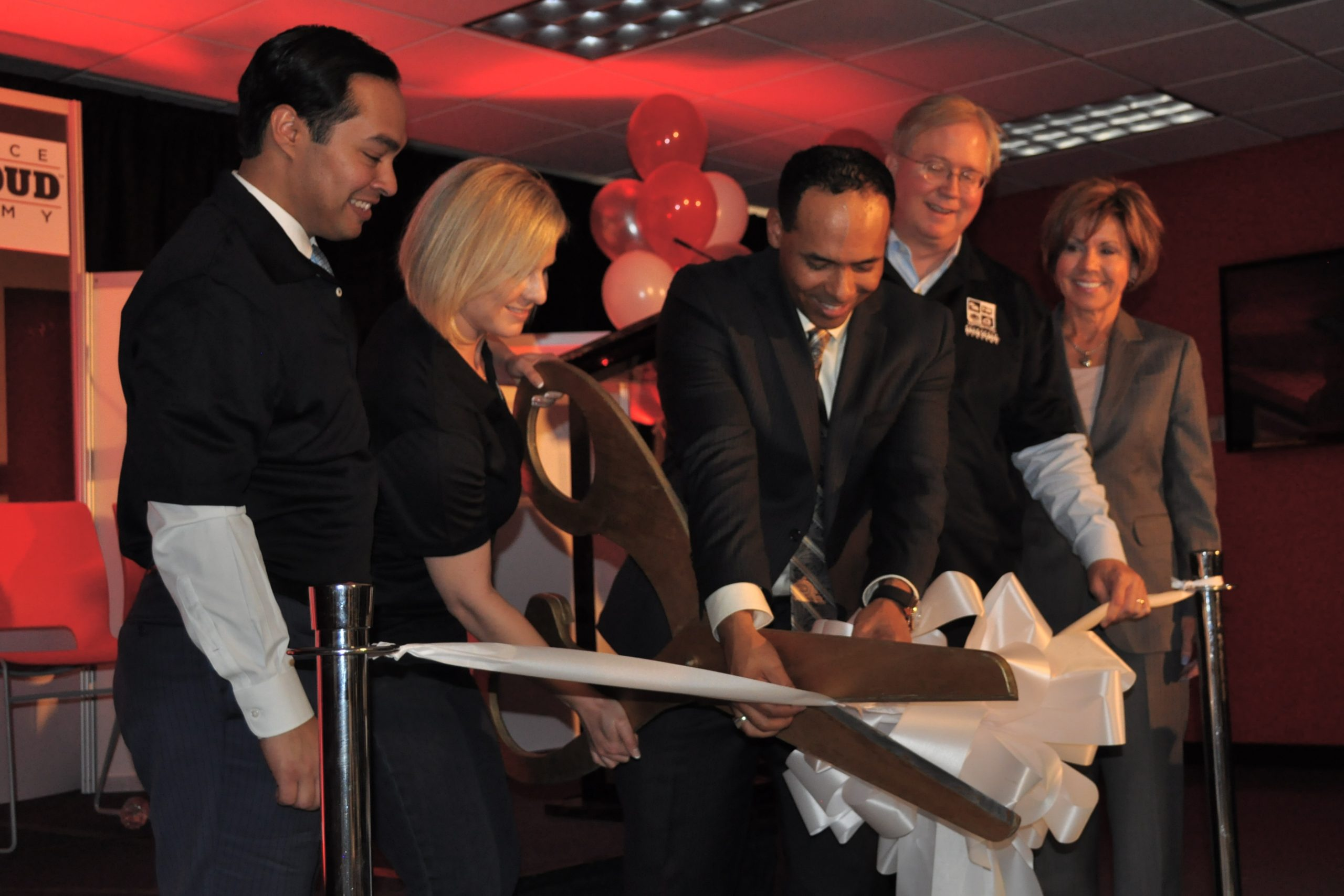 From Left: MayorJulián Castro, Open Cloud Academy Project Manager Debra Carter, Rackspace Learning and Development Director Duane La Bom, Rackspace Co-founder and Chairman Graham Weston, and City Manager Sheryl Sculley share a laugh while struggling to cut the ribbon, officially opening Rackspace's Open Cloud Academy at the Weston Centre.