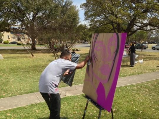 """Michael Arguello, aka """"Composure,"""" paints a portrait during the conference."""