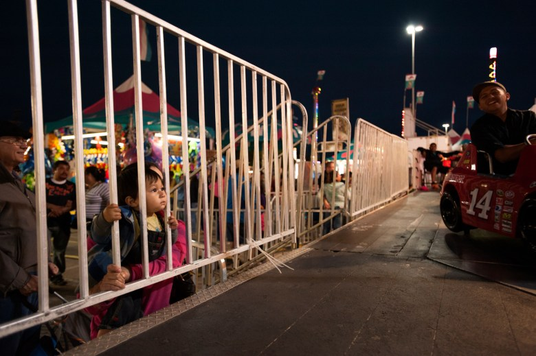 One-year-old Eliah Reyes watches his father and brother on the race-track on Thursday night, unable to ride because of height requirements. Photo by Corey Leamon.