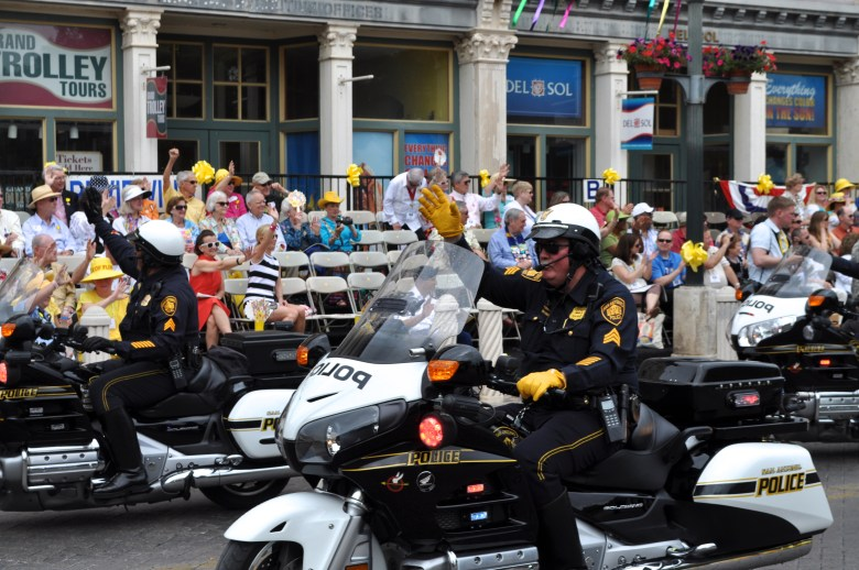 Officers of the San Antonio Police Department Motorcycle Unit wave while riding through Alamo Plaza during the Battle of the Flowers parade (2013). Photo by Iris Dimmick.