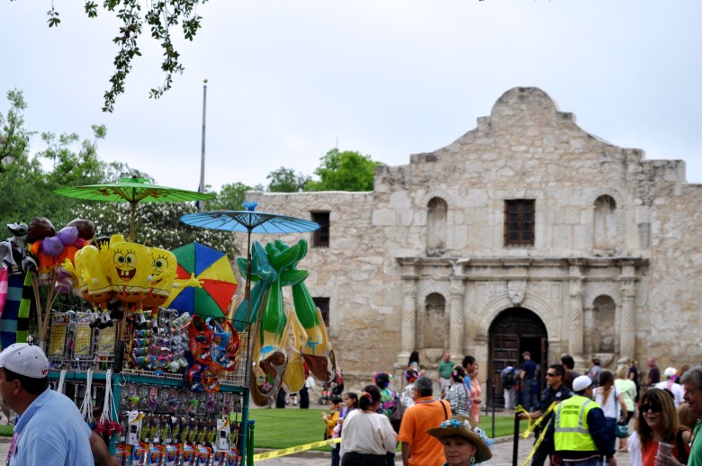 A street vendor pulls his cart of ... unrelated merchandise infront of the Alamo before the 2013 Battle of the Flowers Parade. Photo by Iris Dimmick.