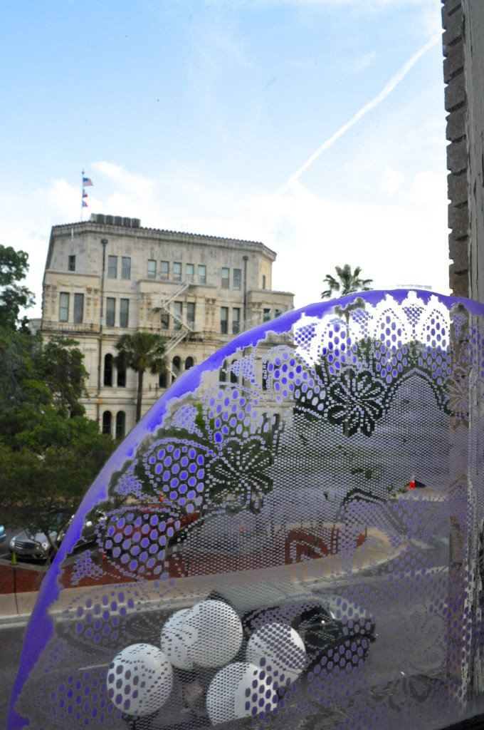 A view of City Hall from the second floor of 201 W. Commerce, through the window art of David Almaguer. Photo by Iris Dimmick.