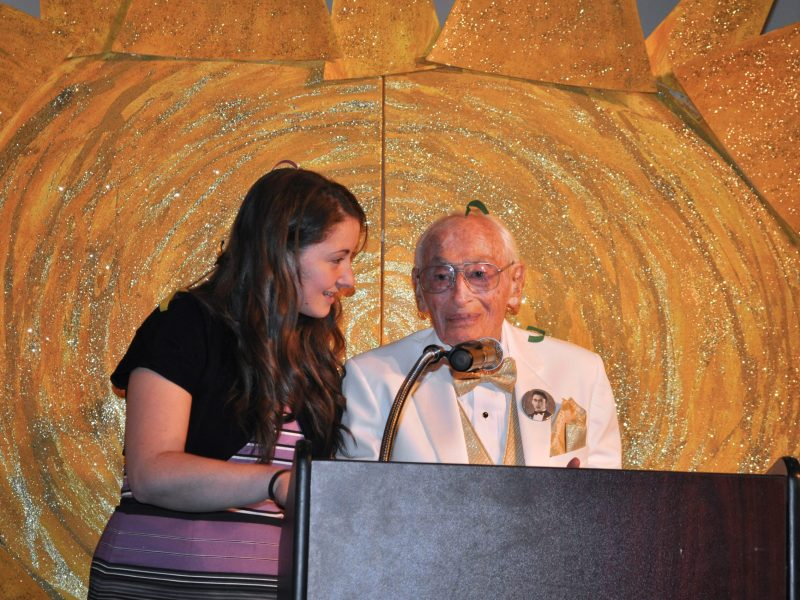 A confetti covered Bill Sinkin address his guests at his 100th birthday celebration. Photo by Iris Dimmick.