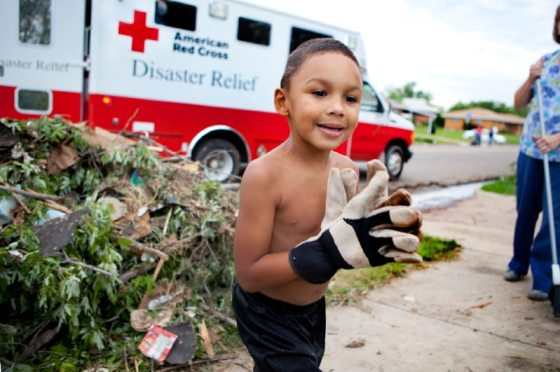 May 21, 2013. Moore, Oklahoma. 4-year-old Devion Hambrick's eagerness to help his family characterizes the collaborative spirit of Moore, Oklahoma, in the aftermath of the tornado. With his father's work gloves, Devion spends all day helping to clear debris from the front yard. Many Oklahoma residents actively partake to help their fellow friends, neighbors, and even strangers. Photo by Talia Frenkel/American Red Cross.