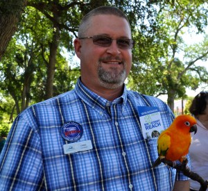 Zoo Operations Manager Chris Vansaike poses for a photo with Cindi Lauper, an adult sun conure that resides at the Zoo. Photo by Iris Dimmick.